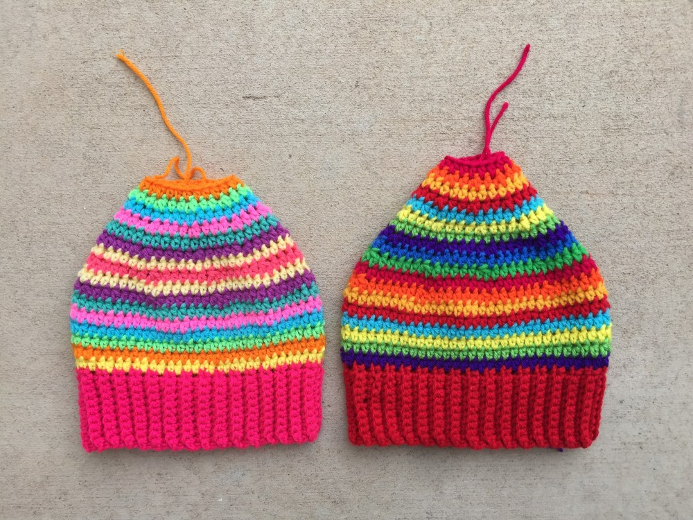 Two nearly completed striped crochet hats made from scrap yarn in  need of a few more rounds and braids