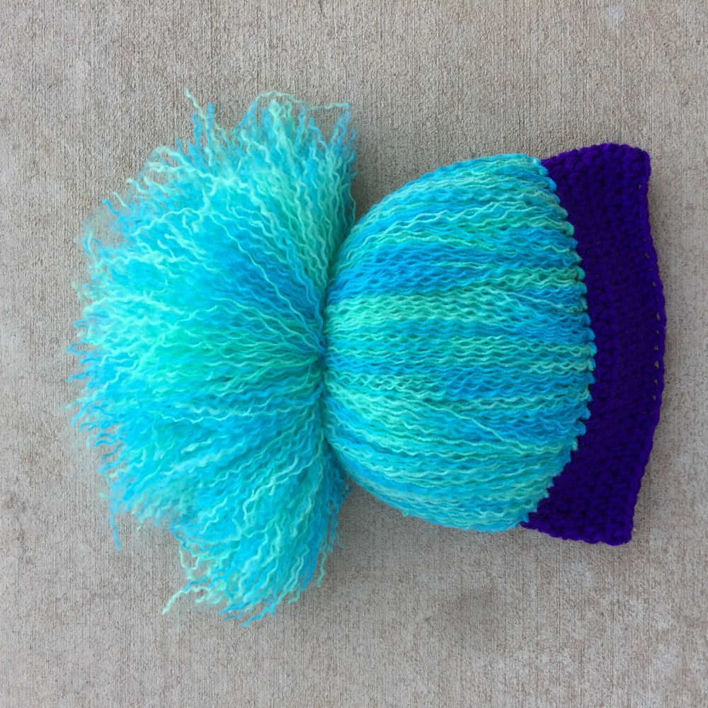 The yarn troll hair combed out and pulled into a pony tail.