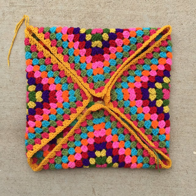 A great granny square blanket to-be with the  corners folded in