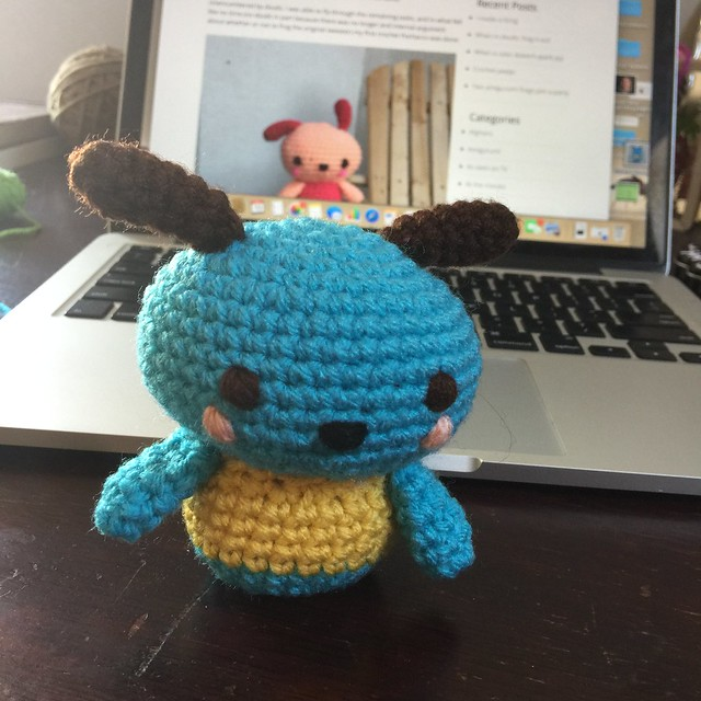 A turquoise crochet Pochacco in the foreground waiting to be finished with an image of the completed light coral Pochacco in the background