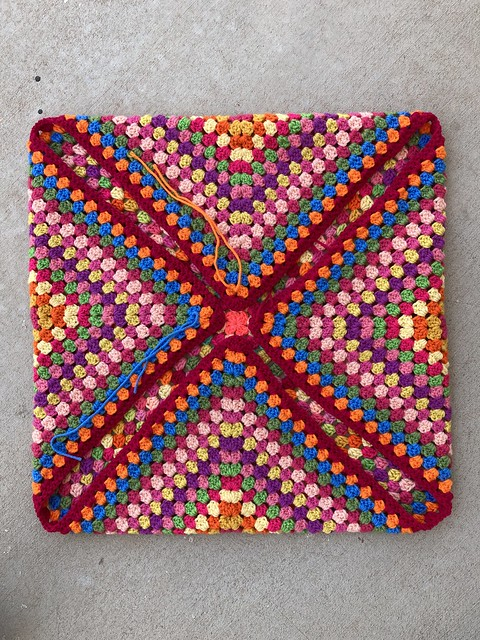 Thirty-two rounds of a multicolor crochet granny square with the ends folded in