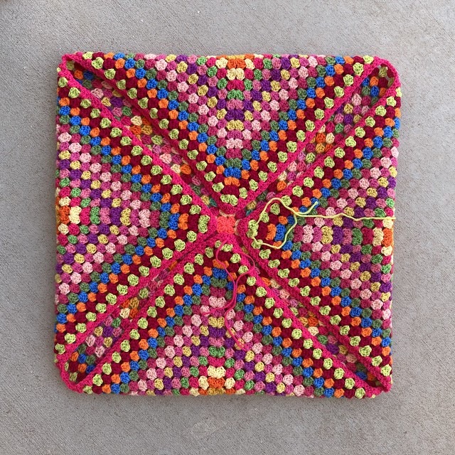 A thirty-four round multicolor crochet granny square with the corners folded in