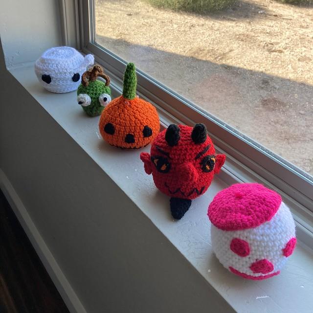 Frive crochet heads: a mummy, a shrunken head, a pumpkin head, a devil head, and a skeleton head