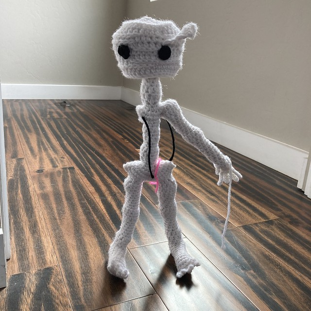 Mr. Headz the crochet skeleton with one arm and wearing his crochet mummy head