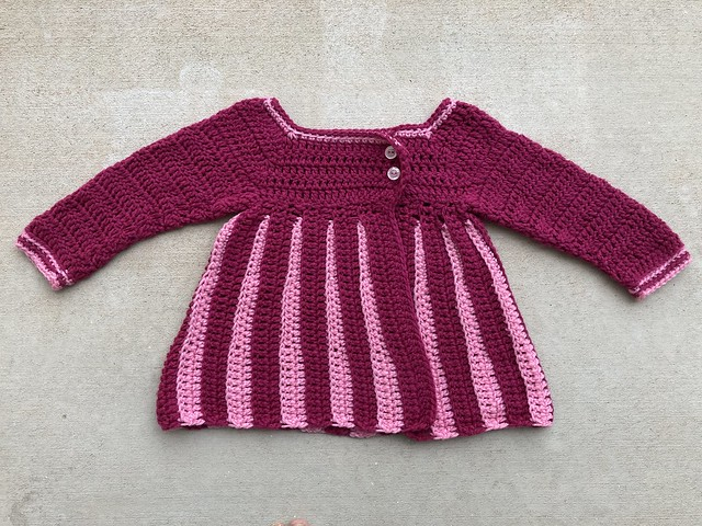 The completed pink and plum pleated crochet sweater