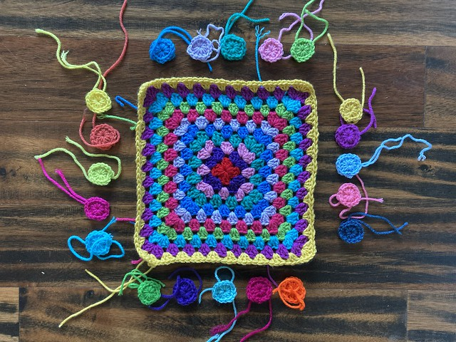An eleven round granny square with twenty one-round granny squares