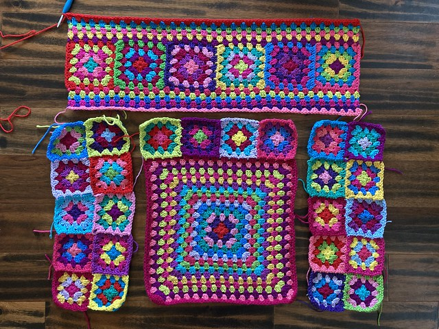 The pieces of a granny square cardigan with a gazillion color changes