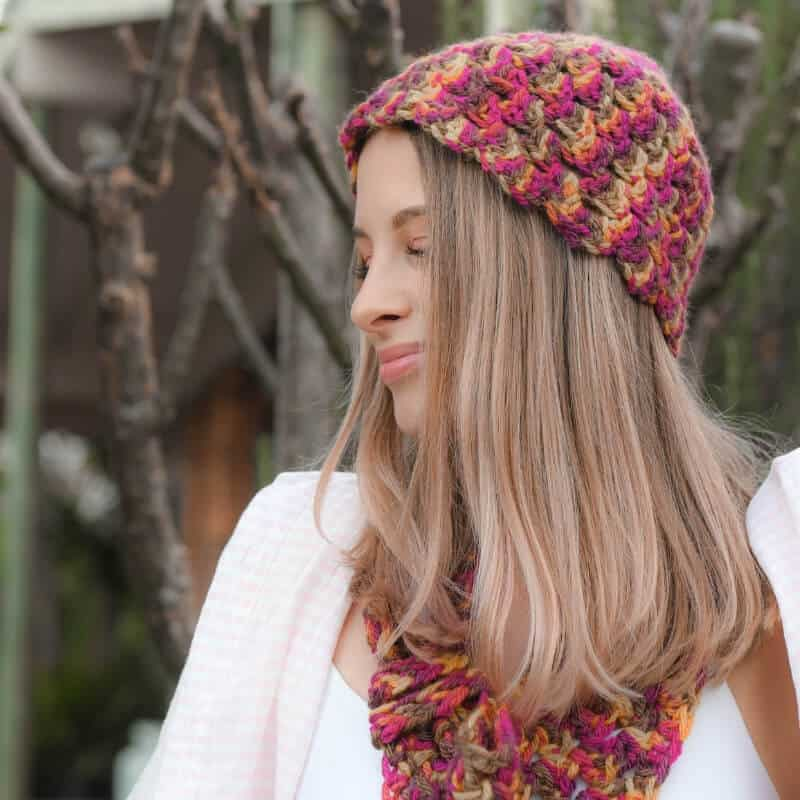 Photo of a woman wearing the Popcorn Cozy Beanie with a matching colorful scarf