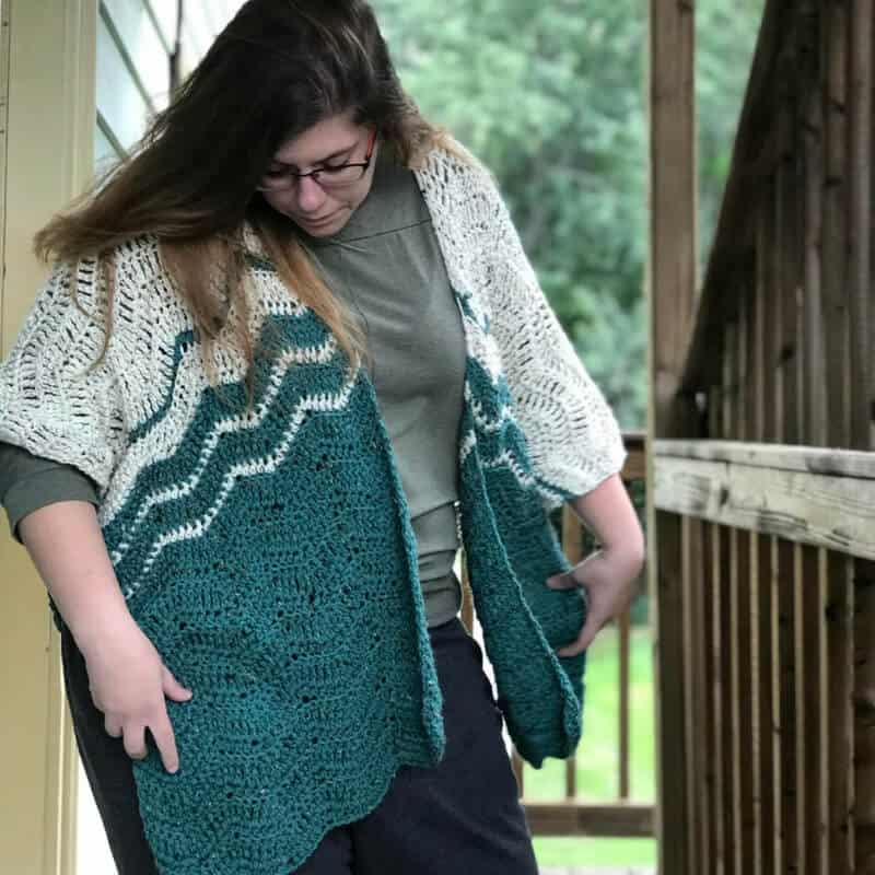 Photo of a woman wearing glasses and the crocheted Ripple Blanket Wrap