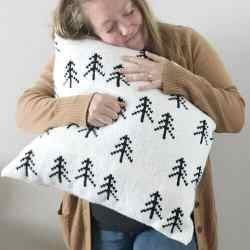 A woman hugging the crocheted Nordic Tree Pillow