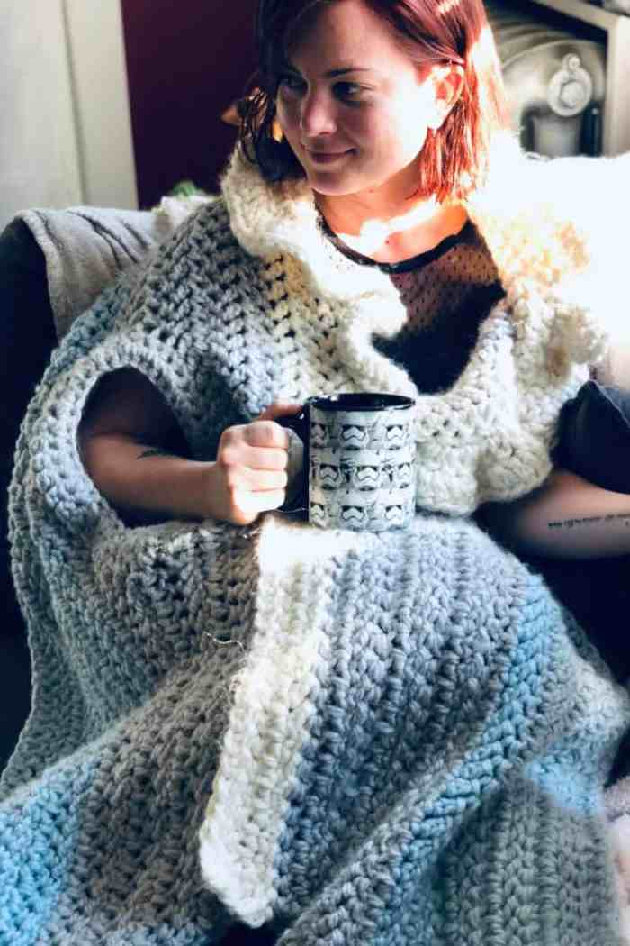 Photo of a woman sitting on a sofa holding a cup and wearing the crocheted Sleigh Ride Wrap