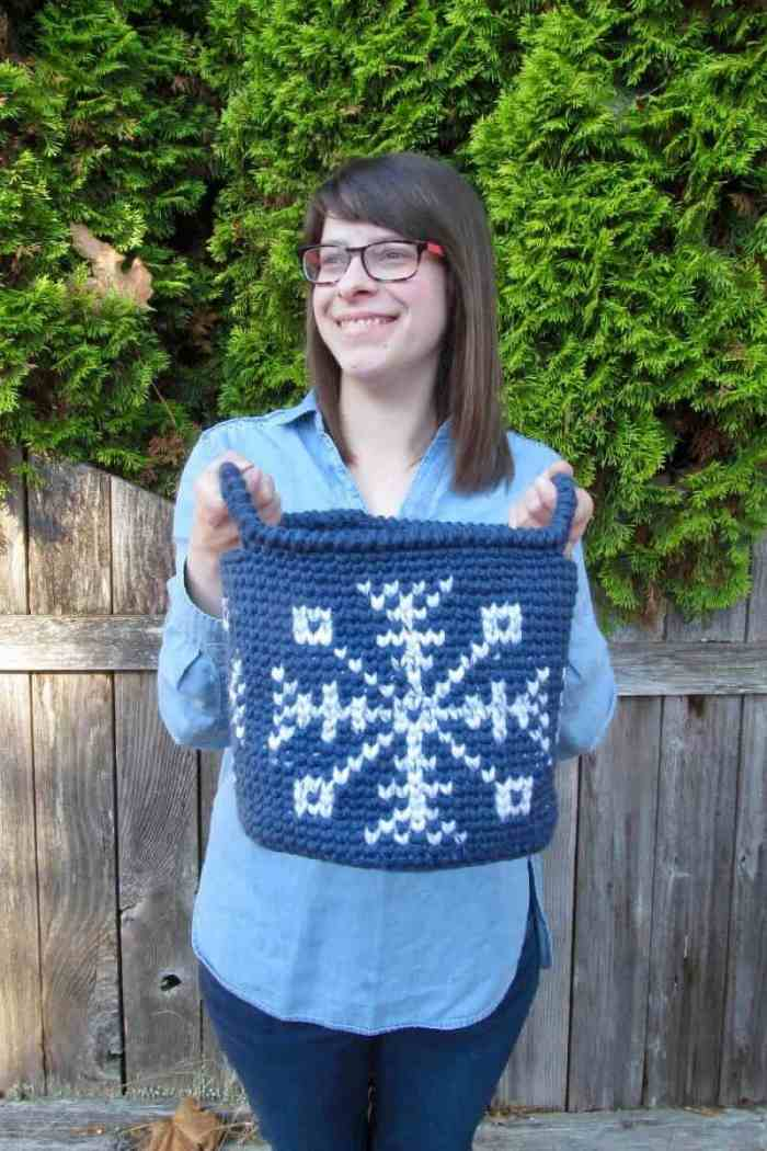 A photo of Sarah LarRieu holding the blue crocheted Let it Snow Tapestry Basket