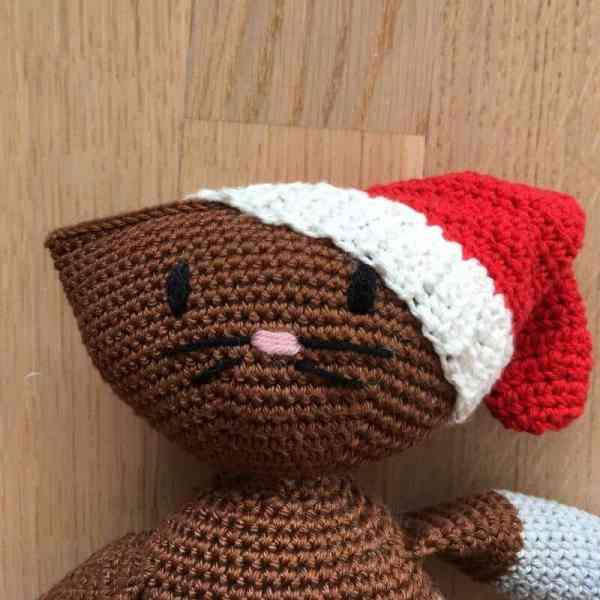 Close up photo of the face of this crocheted amigurumi stuffed animal wearing a Santa hat