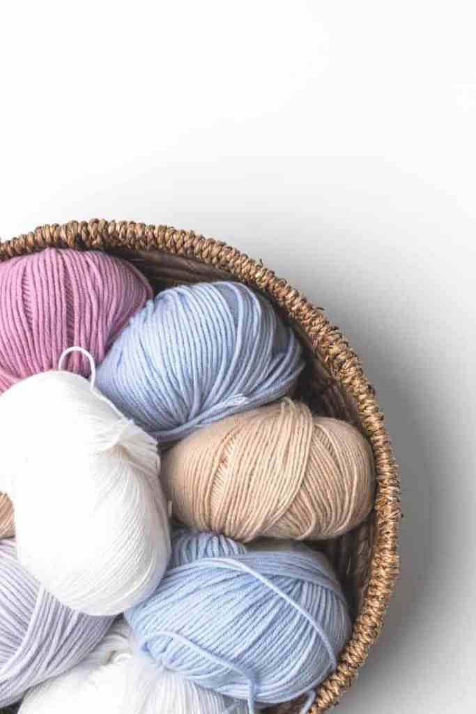 A woven basket full of pastel-colored yarns