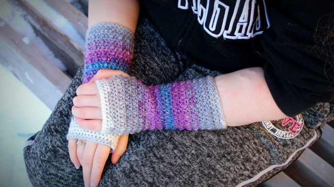 Women wearing a pair of gradient crochet fingerless gloves with her hands in her lap. The colors gradient from white, to gray, to purple, to blue, and back again.