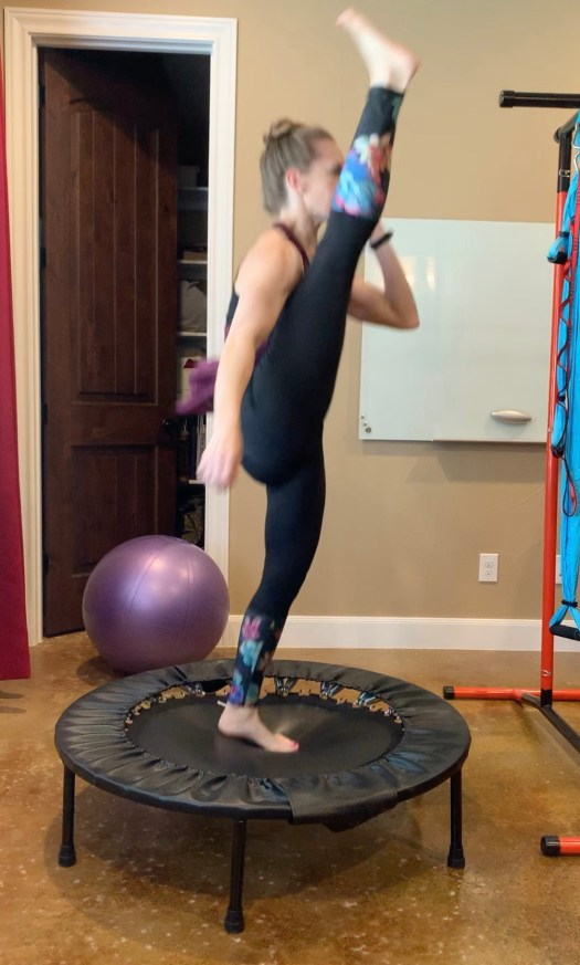 Stephanie doing a high kick, dynamic stretching on her Cellercise rebounder