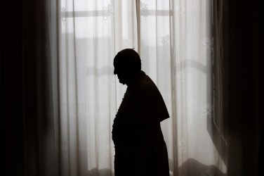 Pope Francis is silhouetted against window light at the end of a meeting at the Vatican