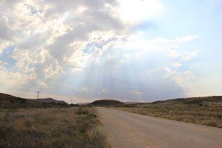 Carretera con los rayos de sol atravesando las nubes