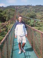 Yo caminando de frente en un puente colgante con la vegetación a ambos lados