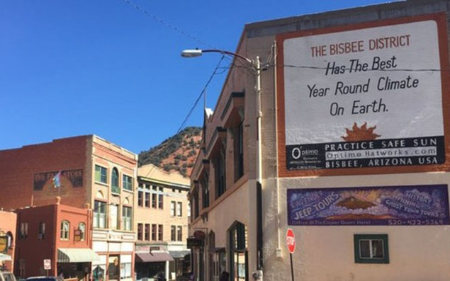 """Bisbee's iconic saying, """"The Bisbee District Has the Best Year Round Climate On Earth,"""" is written on the side a building along Main Street. That may be true, given the clear skies and 65-degree weather the town regularly experiences. (Photo by Diego Mendoza-Moyers/Cronkite News)"""
