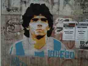 """Grafiti en homenaje a Diego Armando Maradona, """"el Pelusa"""", vestido con la camiseta del equipo nacional, en la Calle Doctor del Valle Iberlucea, en La Boca (Buenos Aires, 2014)"""