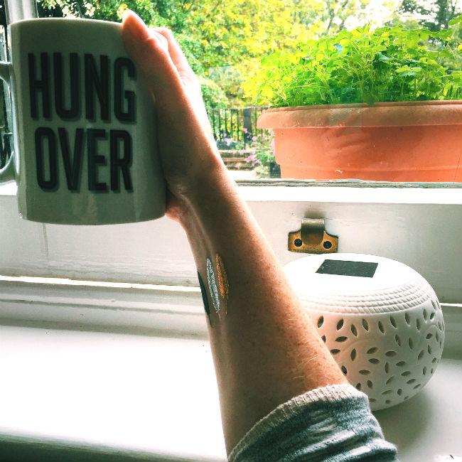 arm with mug that says 'hungover'