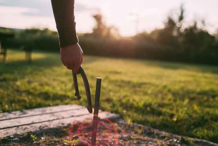 photo of person s hand holding a horseshoe next to metal stake in the ground