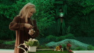 I have no idea who that guy is but Melanie is smiling at a grave, shrouded by green