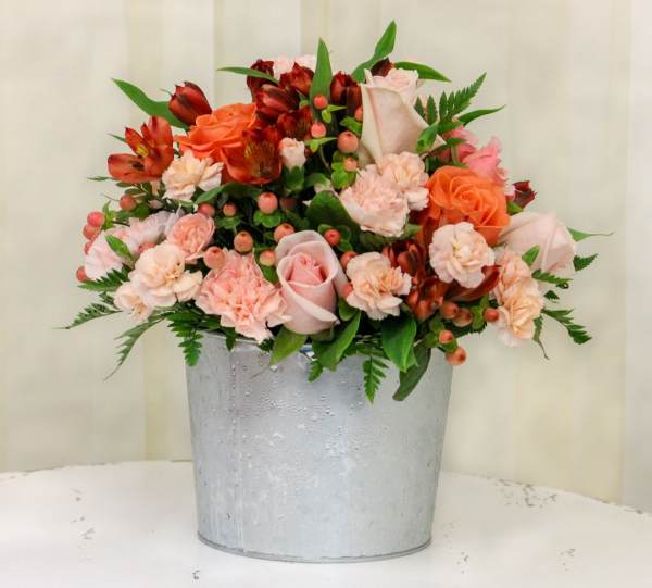 peach, orange, and blush pink roses in a tin bucket