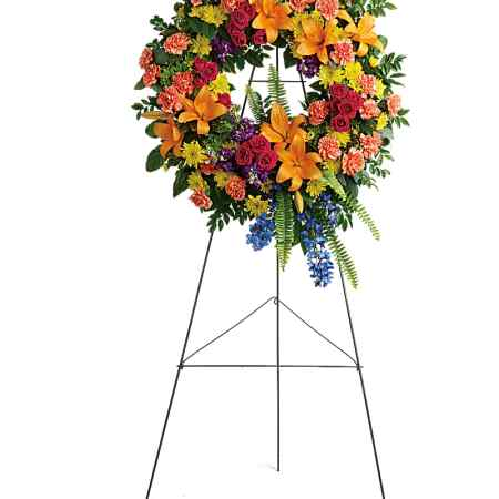 A wreath with tropical flowers in shades of pink, red, orange, and yellow