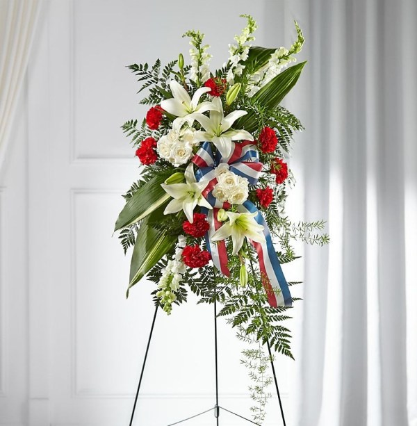 A patriotic spray with red, white, and blue flowers fit for any veteran's funeral