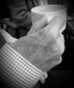 Elderly man with cup of tea with his community