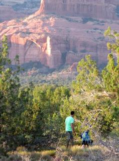 2 people walking under tress with red cliffs of Sedona in the background. This symbolizes attentiveness in nature practice to help participants discover nature as a portal to spiritual awareness.