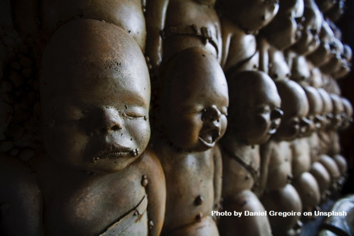 The truth about pain is that some of it comes from hereditary curses. This image shows  rows and rows of weird, hairless statues of infants that one might see in some voodoo type ritual.