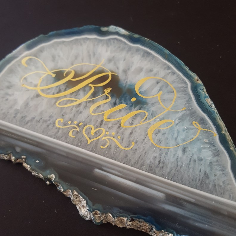 """""""Bride"""" written in calligraphy in gold ink on an agate slice."""