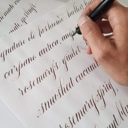 Cursive pointed pen calligraphy in brown ink on a white page. A hand in the upper right hand corner is holding a calligraphy pen.