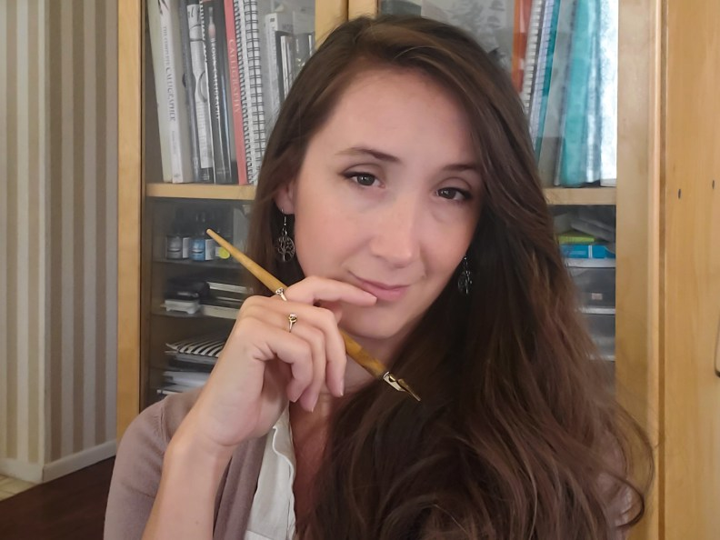Renee, pen in hand, considering ideas she's getting from clients who contact her.
