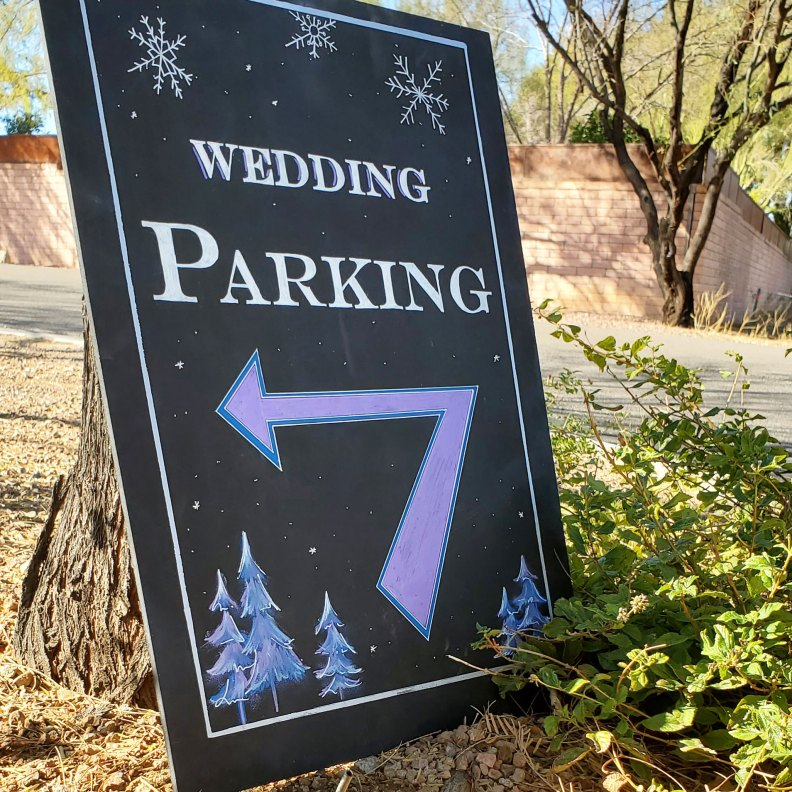 """White lettering on a black chalkboard reads, """"Wedding Parking"""". There is a purple directional arrow in the middle of the sign. Blue and purple artistic trees adorn the bottom corners of the sign; there are snowflakes drawn throughout the background."""