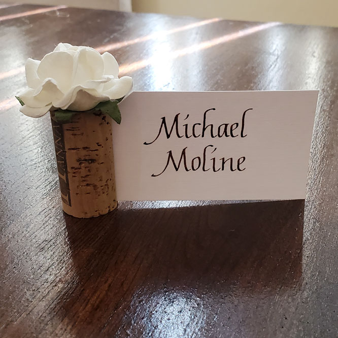 Brown Italic Calligraphy on a white card. The card is held upright by a decorative wine cork .