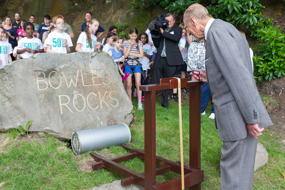 Prince Philip cutting a ribbon on a time capsule at the Bowles outdoor education centre to mark their 50th anniversary.