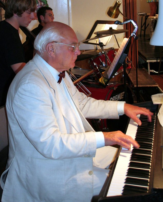 Photo of Derek Watmough MBE at the piano. Mucusian and Crowborough teacher.