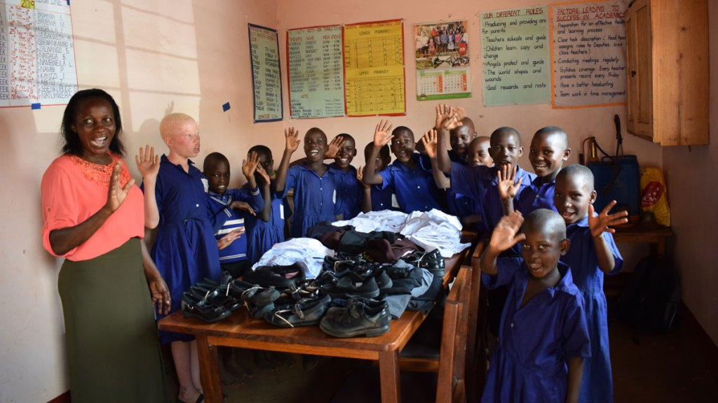World in Need school class with donated shoes and clothes