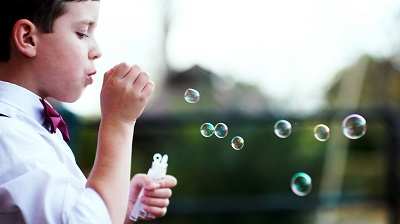 Boy Blowing Bubbles With Bow Tie Outside