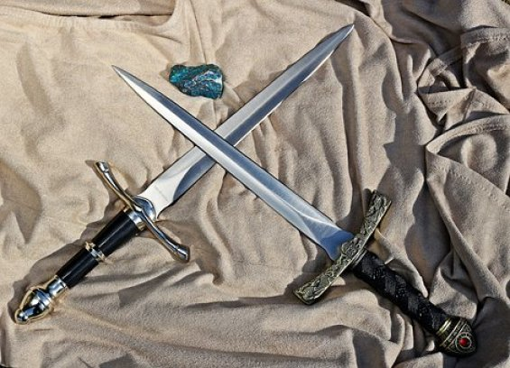two blades crossing with a stone between them
