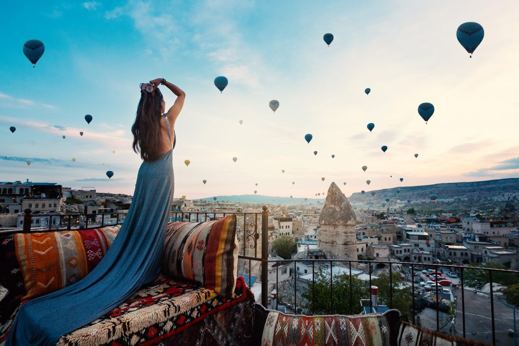 young beautiful woman wearing elegant long dress front cappadocia landscape sunshine with balloons air turkey 1024x683 1
