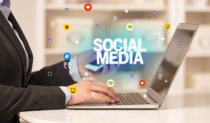 Freelance woman using laptop with SOCIAL MEDIA inscription,