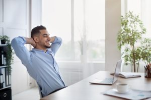Confident Arab Company Employee Leaning On Chair With Hands Behi