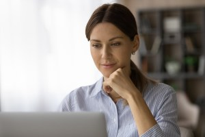 Head Shot Of Confident Focused Woman Looking At Laptop Screen