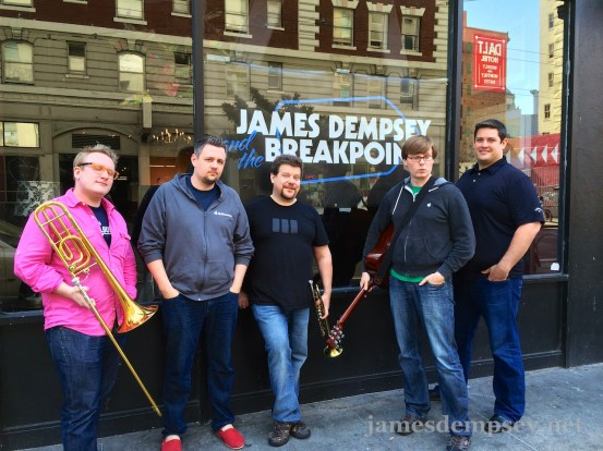 Sam Davies, Ben Scheirman, Daniel Pasco, Jonathan Penn and Nathan Eror stand outside the venue in front of a James Dempsey and the Breakpoints banner