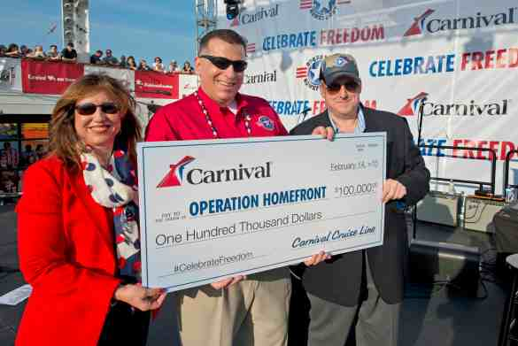Carnival Cruise Line President Christine Duffy, left, Operation Homefront CEO Tim Farrell, center, and Carnival Senior Cruise Director John Heald hold a large check facsimile just prior to a Martina McBride Carnival LIVE concert